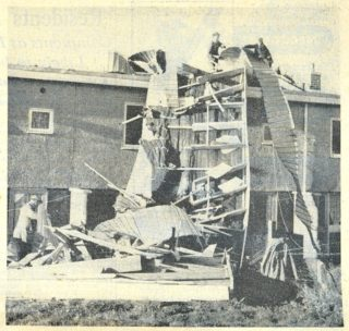 Workmen helping to remove roofing material from houses damaged by the wind | Herts Advertiser, 8 November 1957 page 3