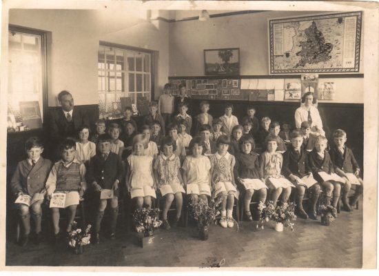 A class at Newtown School c.1936.  Mr Cox the Head Master is the teacher on the left.  4th from the left in the front row is Nellie Bates who was about 10yrs old when the photo was taken.