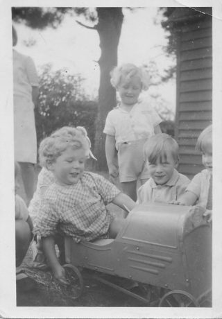 Children playing outside the building. Brian McCoy in the pedal car c1940 | Brian McCoy